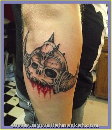 ugly-alien-skull-face-tattoo-on-elbow